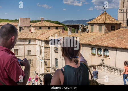 Tourists in Old Town of Girona with Basilica de Saint Feliu in the background, Catalonia, Spain - Stock Photo