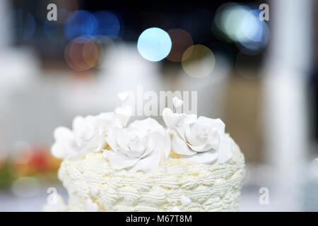 White wedding cake detail - marzipan decorative flowers and hearts - Stock Photo