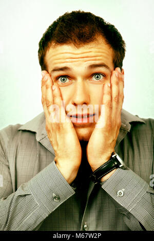 Worried young man face looking scared and anxious - Stock Photo