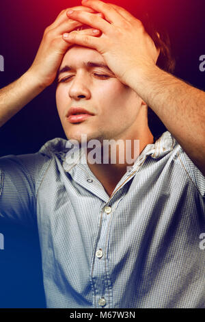 Tired stressed young man suffering from headache or hangover - Stock Photo