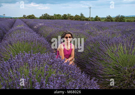 Woman in lavender field smiling, near the village of Valensole. Located in the Provence region, southeastern France. - Stock Photo