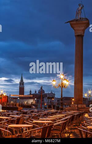 Empty cafe chairs at St. Mark's Square in Venice, Italy just before dawn - Stock Photo