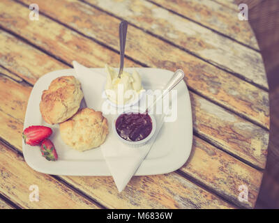 Vintage filtered shot of cream tea with scone and jam on a table - Stock Photo