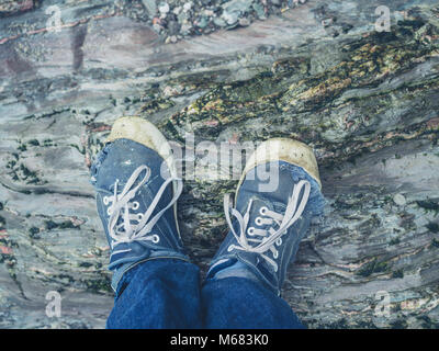 The feet of a young man wearing trainers standing on the rocks - Stock Photo