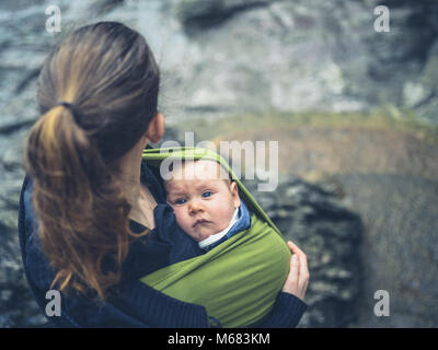 A young mother is standing outside in nature with her baby in a sling - Stock Photo