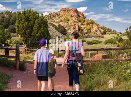Young woman with two children walking around Garden of the Gods park in Colorado Springs, Colorado; rock formations - Stock Photo