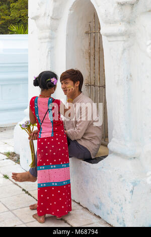 Girl applying thanaka on cheek of man at Kuthodaw Pagoda, Mandalay, Myanmar (Burma), Asia in February - Stock Photo