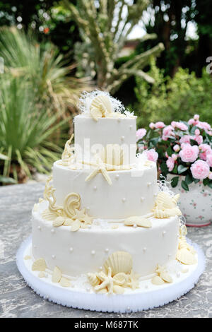 White wedding cake decorated with marzipan shell and starfish - Stock Photo