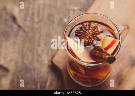 hot spicy beverage. Hot drink (apple tea, punch) with cinnamon stick and star anise. Seasonal mulled drink. - Stock Photo