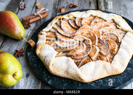 Pie with apples, pears and cinnamon on an old wooden background. Apple tart - Stock Photo
