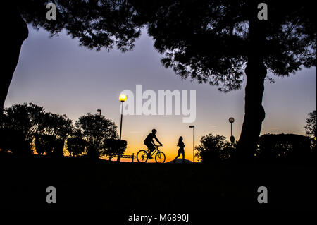 Argeles-sur-Mer (south-eastern France). Two young people riding a mountain bike and running along the waterfront - Stock Photo
