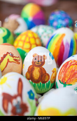 Detail of colorful painted Easter eggs with different forms and animals. In that case, a bear. - Stock Photo