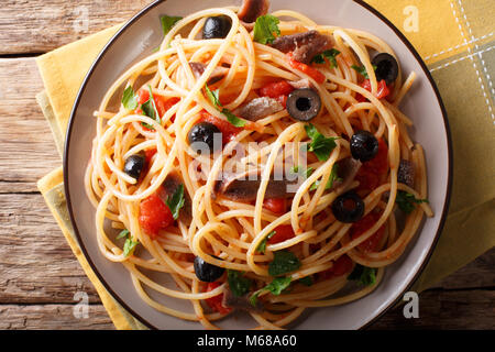 Pasta Alla Puttanesca with anchovies and black olives on a plate. horizontal top view from above - Stock Photo