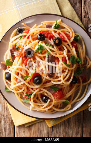 Pasta Alla Puttanesca with anchovies and black olives on a plate. Vertical top view from above - Stock Photo