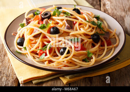 Delicious spaghetti alla putanesca with anchovies with vegetables and greens close-up on a plate. horizontal - Stock Photo