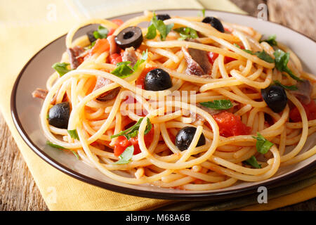 Spaghetti alla putanesca with anchovies, tomatoes, garlic and black olives close-up on a plate. horizontal - Stock Photo