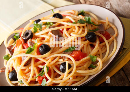 Italian food: spaghetti alla putanesca with anchovies, tomatoes, garlic, black olives and greens close-up on a plate. - Stock Photo