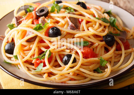 Pasta Alla Puttanesca with anchovies and black olives macro on a plate. horizontal - Stock Photo