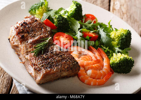 Beef steak with prawns and broccoli, tomatoes, arugula closeup on plate on table. Horizontal. Surf and Turf. - Stock Photo