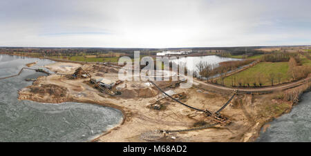 Composite panorama of aerial photographs and aerial photos of a wet quarry for gravel and sand with an almost frozen - Stock Photo