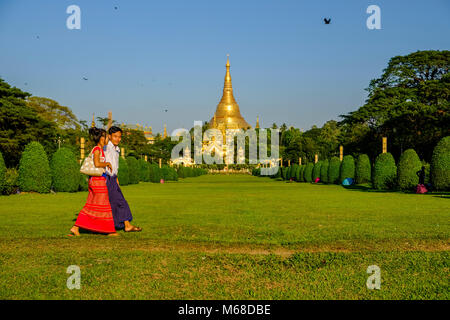 A young couple is walking on a meadow in front of the golden Shwedagon pagoda, the most sacred pagoda of Myanmar, - Stock Photo