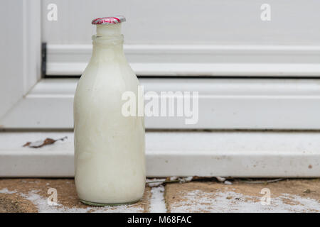 British Milk Bottle on Doorstep - milk frozen - Stock Photo