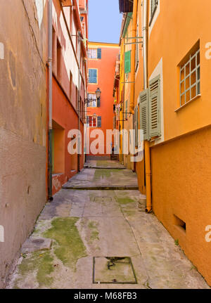 Narrow courtyard among classic mediterranean colorful buildings in Nice, France - Stock Photo