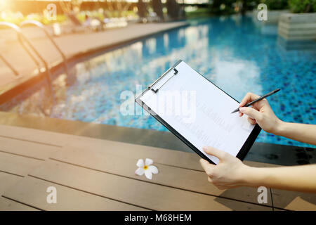 Focus on document, girl fills empty paper on background of pool. Front used with Open Font License - Stock Photo