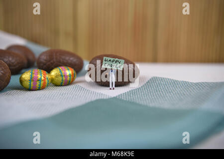 happy Easter words with chocolate Easter eggs and cute miniature person figurine - Stock Photo