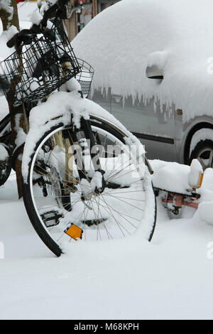Parked cars and bicycles covered by the snow, space for text - Stock Photo