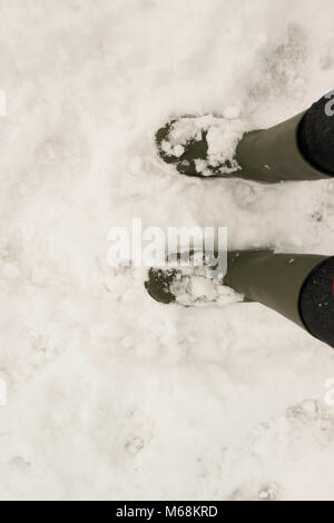 A person wearing a pair of traditional green rubber wellington boots on the snow.  Personal point of view, space - Stock Photo