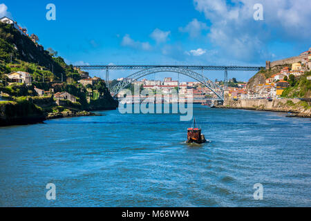 Rabelo Boat on the Douro River approaching the Dom Luis I Bridge in Porto Portugal - Stock Photo