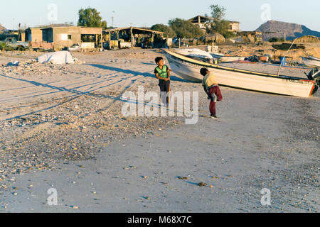 two small Mexican boys play throwing stones into sea from beach where fishing boats are pulled up & shore is lined - Stock Photo