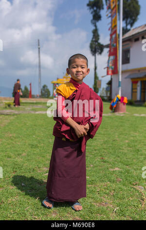 Pelling, India - April 26, 2017: Unidentified young novice buddhist monk in traditional red robes standing in front - Stock Photo