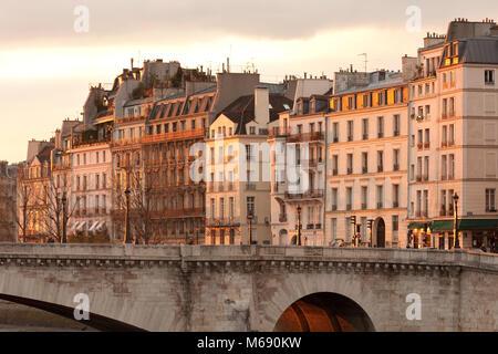 Facades of apartment buildings at Ile Saint Louis and Pont de la Tournelle bridge, Paris, France - Stock Photo