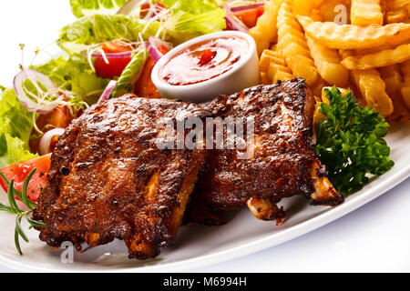 Grilled ribs, French fries and vegetables on white background - Stock Photo