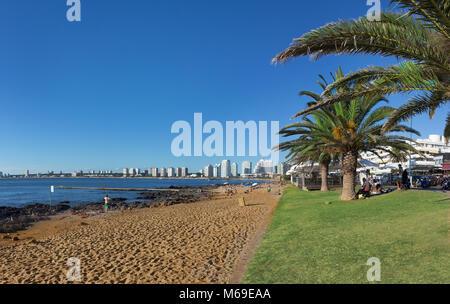 Punta Del Este, Uruguay - February 26th, 2018: People at the beach located beside the Rambla Gral Jose Artigas and - Stock Photo