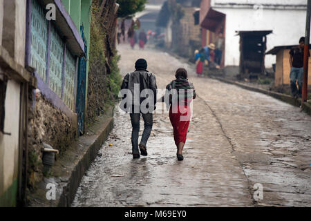 An indigenous Ixil Maya man walking, holding hands with his wife on a rainy day in San Gaspar Chajul, Ixil Triangle, - Stock Photo