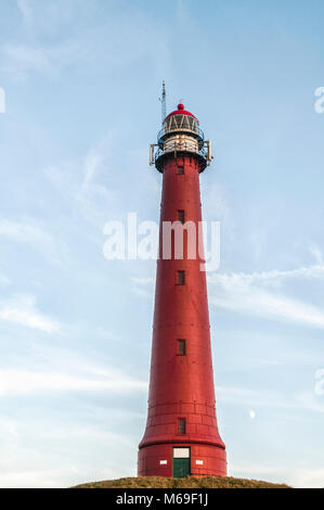 Dutch lighthouse placed on top of a hill against a blue cloudy background - Stock Photo