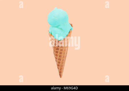 Pistachio ice cream cone on faded pastel color background. Ice cream in wafer cup. - Stock Photo