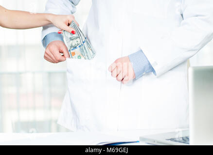 Female hand putting money in doctor pocket. Doctor accepting bribe. - Stock Photo