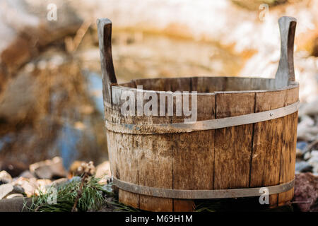 The old wooden tub is standing by a small pond on the background