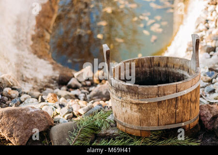 Old wooden bath tub near the pond in the autumn in the yard