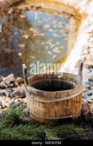 A wooden tub from a bath stands on stones in the yard on pine trees near a small pond