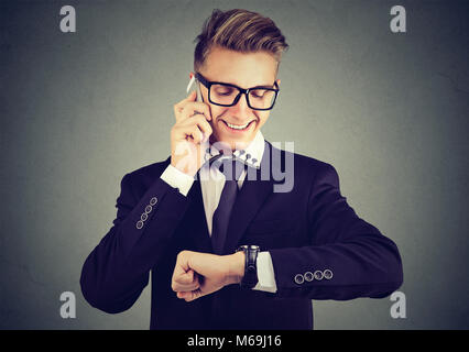Handsome young smiling man in suit and glasses checking time while having phone call. - Stock Photo