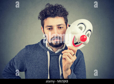 Young bearded upset man covering personality with happy clown mask on gray background. - Stock Photo