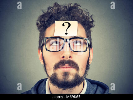thinking man with question mark looking up on gray wall background - Stock Photo