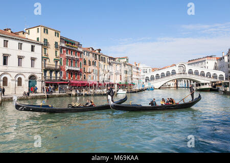 Two gondolas with tourists on the Grand Canal with the Rialto Bridge and Riva del Vin, San Polo, Venice, Veneto, - Stock Photo