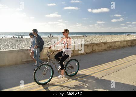 Attractive woman wearing sunglasses, pedaling bicycle along popular beachside paved boardwalk in Mission Beach, - Stock Photo