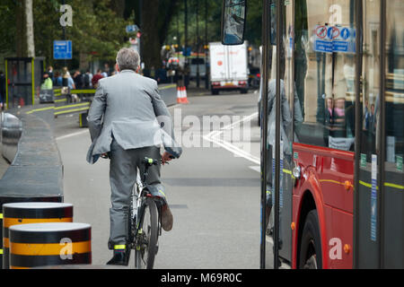 A businessman in a business suit rides a bike through the streets of London. - Stock Photo